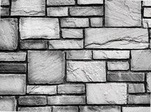 Black and white, old rough textured paved brick wall. Genuine old weathered, and textured rough brick wall with bricks of different sizes. Urban or country Stock Images