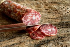 Genuine salami. Sliced on ancient wooden table Stock Photo