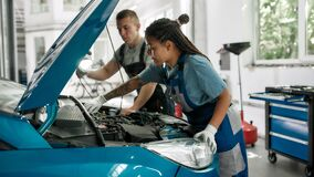 Free Genuine Services. African American Woman, Professional Female Mechanic Repairing Car Engine, Tighten, Screw With Spanner Royalty Free Stock Photo - 192254765