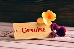 Genuine tag. Tag banner genuine and violet flower on wooden desk royalty free stock photo