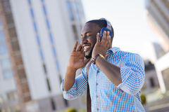 Genuine witty young man liking his new headphones. Music is life. Engaging talented active guy testing new equipment and running some of his track while enjoying Royalty Free Stock Photos