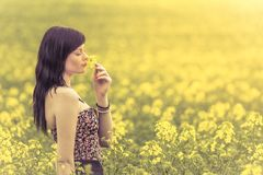 Genuine woman in meadow of yellow flowers sniffing flower. Attractive beautiful young girl enjoying the warm summer sun in a wide green and yellow meadow. Part Stock Images