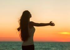 Genuss- freie glückliche Frau, die Sonnenuntergang genießt. Stockfoto