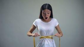 Geobsedeerde vrouw die metend band op haar taillewens, boulimie slank te zijn aanhalen stock video
