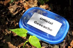 Geocache. Geocaching concept with blue geocache box showing outdoor sports concept Stock Photos