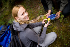 Geocache. A young woman finding a geocache in the forest Royalty Free Stock Photo