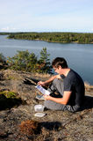 Geocache. A young man finding a geocache Royalty Free Stock Image