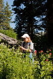 Geocaching. Image of a woman searching for a geocache in the mountains with a GPS unit Stock Images