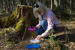 Geocaching in the forest. A woman geocaching in a green forest Stock Photography