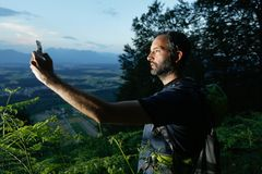 Geocaching. Trekker searching path to cache using global positioning device Stock Photo