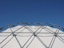 Geodesic exoskeleton tensile dome structure. Over blue sky stock photo