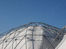 Geodesic exoskeleton tensile dome structure. Over blue sky royalty free stock images