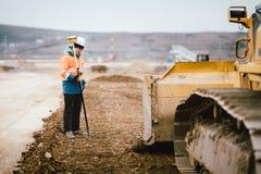 Geodesidetaljer - arbetare för konstruktionsplats som bygger huvudvägen och vägar Granskande teknikerdetaljer royaltyfri foto