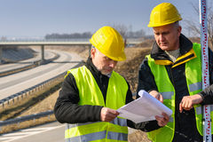 Geodesist a affiché des plans sur le chantier de construction Photographie stock