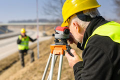 Geodesist measure land with tacheometer highway stock photo