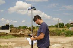 Geodesist que trabalha em um terreno Fotos de Stock