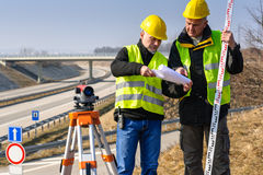 Geodesist read plans on construction site Royalty Free Stock Photos