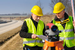 Geodesist two man theodolite stand highway Stock Photos