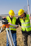 Geodesist two man theodolite stand highway Royalty Free Stock Image