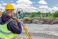 Geodesist werkt met totale post aan een bouwterrein Civi Royalty-vrije Stock Afbeeldingen