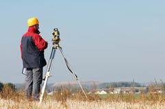 geodesy Inspektörarbetare med teodoliten royaltyfri foto