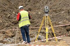 Geodeta przy budową niesie out pomiary zdjęcie royalty free