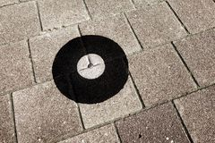 Geodetic survey marker set in a pavement. royalty free stock photography