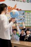Geografia d'istruzione dell'insegnante agli scolari con un globo Fotografia Stock