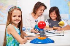 Geografieklasse - kleines Mädchen, das über das Sonnensystem lernt Lizenzfreies Stockbild