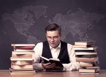 Geografilärare på skrivbordet med högen av böcker Royaltyfria Foton