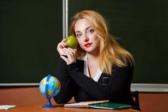 Geografilärare som rymmer ett grönt äpple arkivfoton