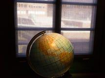 Geografiskt jordklot i det mörka rummet mot ett fönster arkivbild