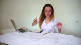 Geographer working with map at home, young female finds ideas using laptop. Young fair-haired wearing home clothes woman sitting near table with big map, ruler stock video
