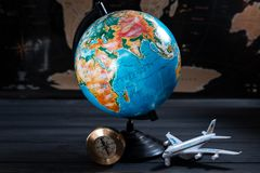 Geographical globe on the background of a black map with a small tourist plane.  stock photo