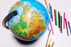 Geographical globe and colored pencils and markers on a white background. Back to school, horizontal view, copy space, kids learn royalty free stock photos