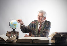 Geography. Senior man studying geography with a globe royalty free stock photo
