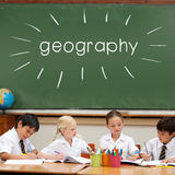 Geography against cute pupils sitting at desk Stock Photos