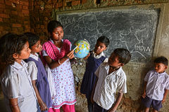 Geography Education. Teacher and students with a globe at the geography class in the rural area of West Bengal -India royalty free stock image