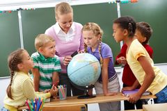 Geography lesson. Portrait of pupils looking at globe while listening to teacher during geography lesson royalty free stock images