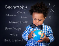 Geography lesson. Closeup portrait of cute little African boy with small globe in hands, preparing to geography lesson, back to school concept stock images