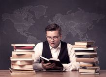 Geography teacher at desk with pile of books Royalty Free Stock Photos