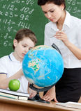 Geography teacher explains something to the pupil. Pointing at the globe Stock Photos