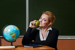 Geography teacher holding a green apple. Stock Photos