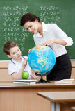 Geography teacher shows something to the pupil. At the terrestrial globe Stock Photography