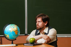 Geography teacher sits in front of a globe. Royalty Free Stock Photo