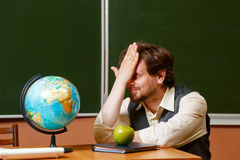 Geography teacher sits in front of a globe. Stock Photo