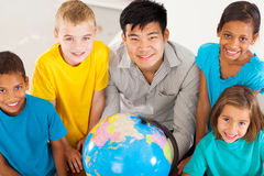 Geography teacher students. Smiling geography teacher with group of adorable primary students Stock Images