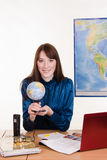 Geography teacher at the table with a globe in her hands Stock Photography