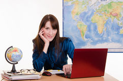 Geography teacher working at a laptop Royalty Free Stock Image