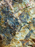 Geologic Rock. Multiple layers of geologic rock, casting a variety of mineral hues Stock Photo